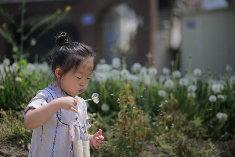 Close-up of girl blowing bubbles while standing on field