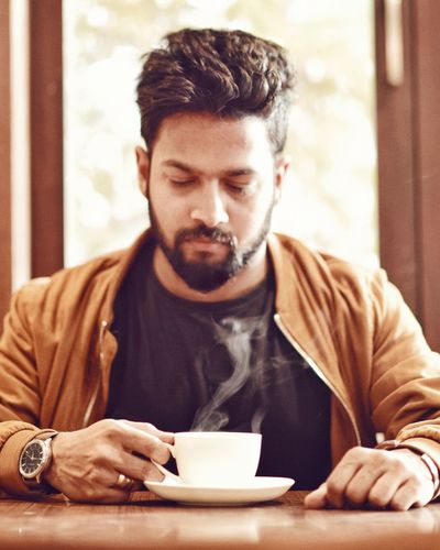 Young man sitting on table with a hot cup of coffee