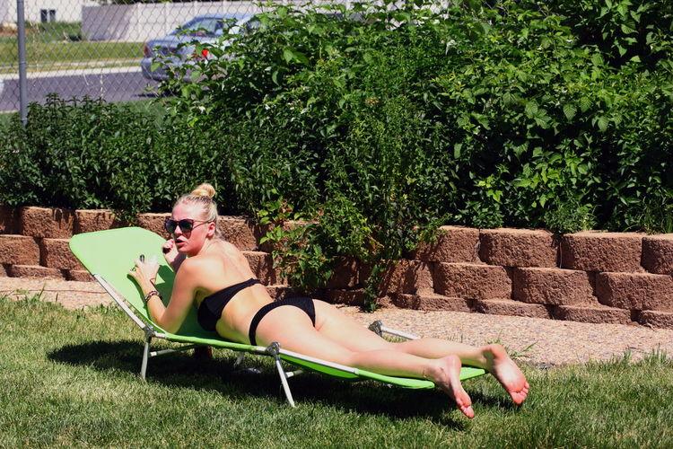 Rear View Of Woman In Bikini Lying On Lounge Chair