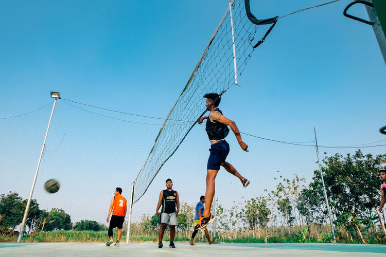 Low angle view of people playing against clear blue sky