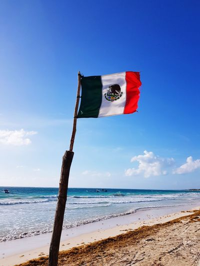 Flag Mexico at tulum beach Windy Caribbean Tulum Mexico Flag Water Sea Beach Red Patriotism Sand Flag Sky Horizon Over Water National Icon Waving Symbolism Fluttering National Flag Coastline Shore Pole