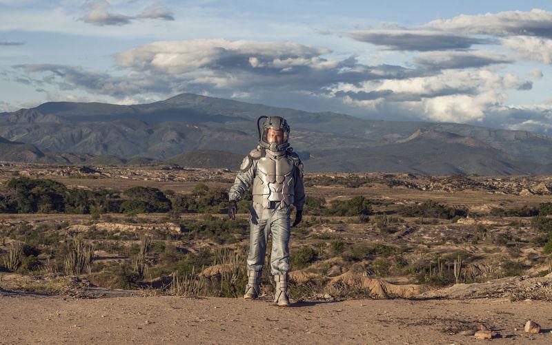 Portrait of man standing on landscape against mountains