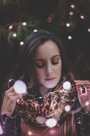 Close-Up Of Beautiful Woman Holding Illuminated Lights