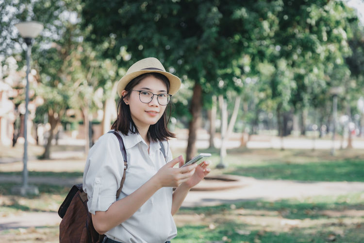 Young woman using smart phone while standing outdoors