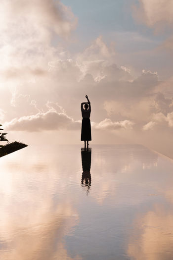 Silhouette Woman Standing On Infinity Pool Against Sky During Sunset