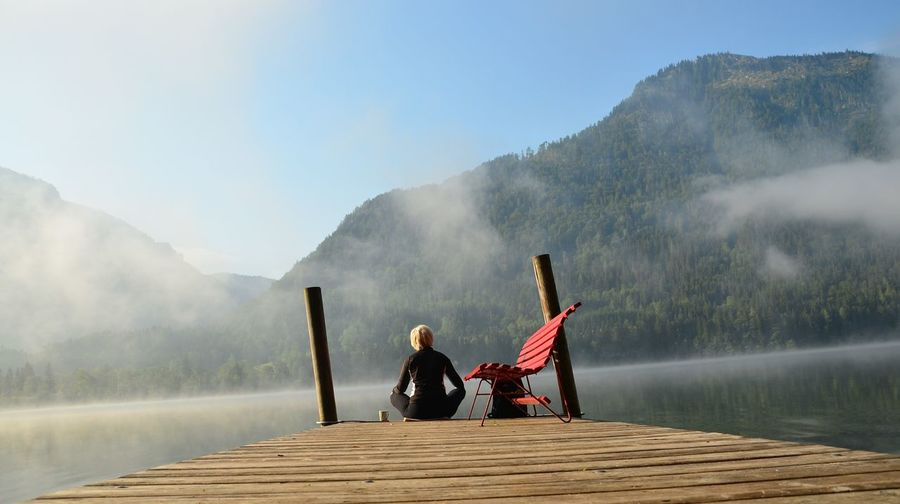 Rear view of woman sitting on pier at lake against mountain