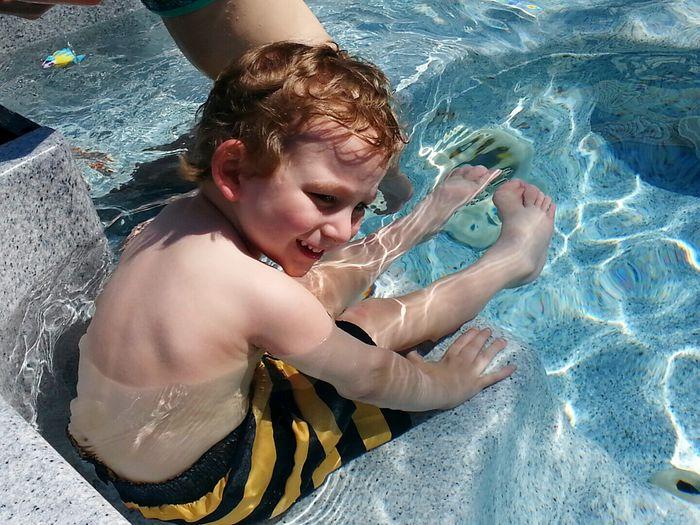 Happy Boy Sitting In Pool