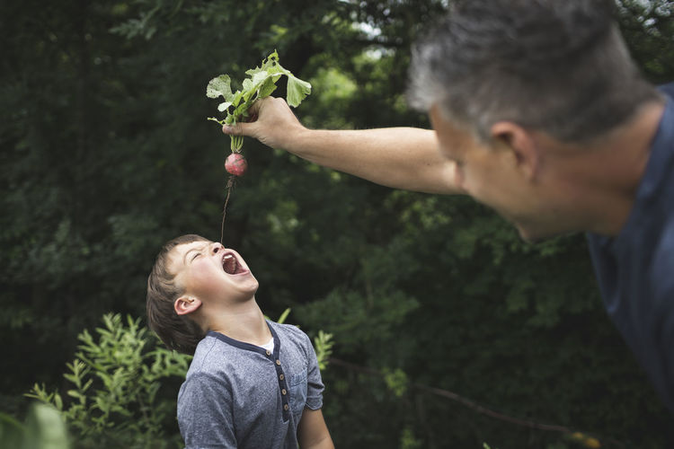 Father and son holding plant
