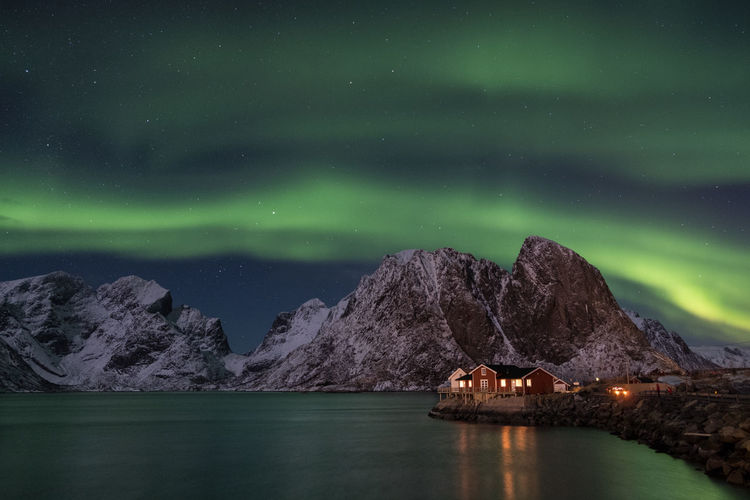 Northern Lights in Reine Artic Aurora Borealis Green Lofoten Islands Northern Lights Norway Reflection Reine Stripes Astronomy Aurora Polaris Beauty In Nature Cold Temperature Europe House Mountain Nature Night Scenics Snow Mountain Stars Tranquility Water Waterfront Winter