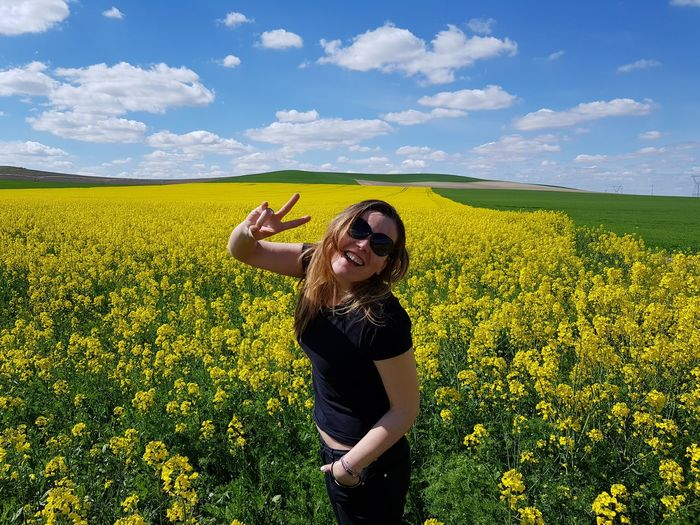 Portrait of happy mid adult woman wearing sunglasses while standing amidst flowers against sky during sunny day