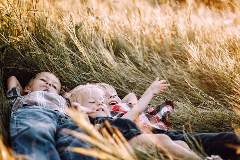EyeEm Selects siblings. Grass Togetherness Child Outdoors Summer Fun Childhood People Day Boys Carefree Lying Down Adult Girls Enjoyment Leisure Activity Portrait Relaxation Females Bonding Fresh On Market 2017