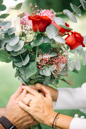 Close-up of couple holding bouquet of red roses