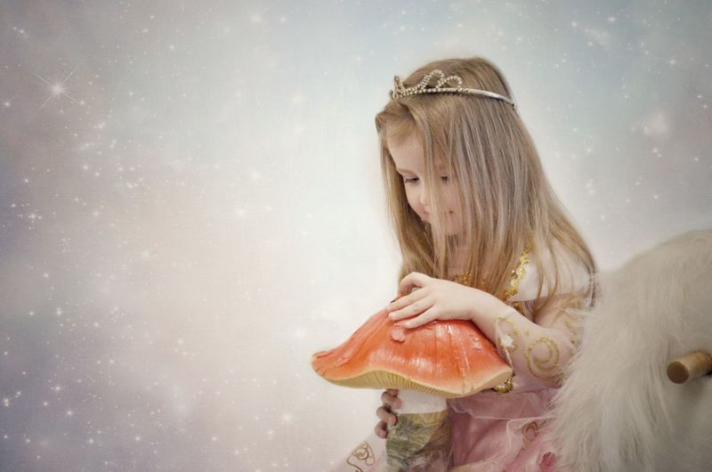 Digital composite image of girl wearing princess costume with artificial mushroom against glittering backgrounds