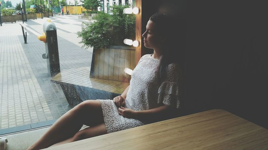 EyeEm Selects Young Women Sitting Women Side View Close-up Thoughtful Looking Through Window Pretty Day Dreaming Plain Background Thinking Posing Window Sill RainDrop
