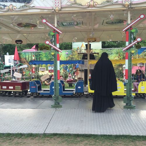 Islamic woman at an amusement park in Berlin. Germany Amusement Park Black Clothes Burqa Burqah Day Islamic Woman One Person Traditional Clothing Woman From Behind