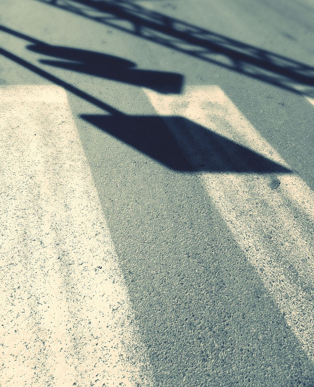 Shadow Of Road Signs On Zebra Crossing