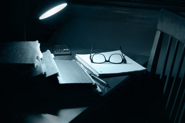 Illuminated lamp with files and eyeglasses on table