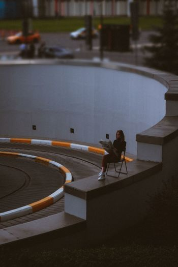 High angle view of man sitting on road