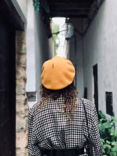 Rear view of woman wearing beige beret