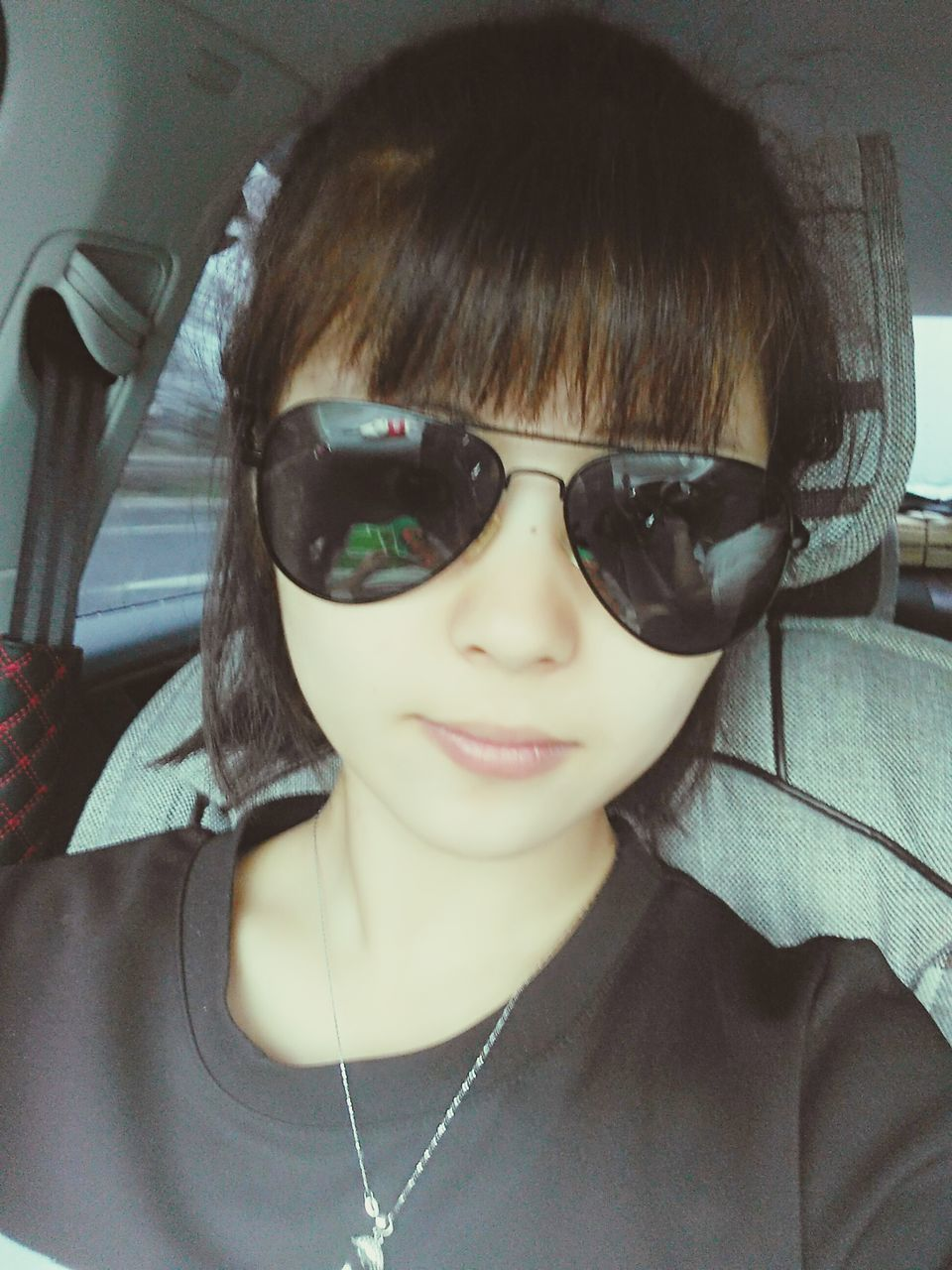 sunglasses, real people, front view, looking at camera, one person, portrait, indoors, eyeglasses, lifestyles, elementary age, leisure activity, casual clothing, headshot, bangs, glasses, young adult, day, childhood, close-up, young women