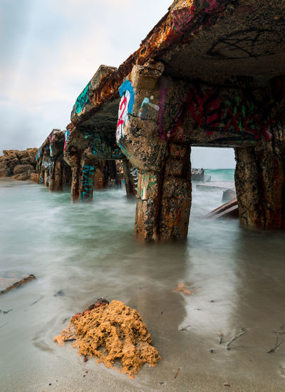 Old bridge ruin Graffiti Ruins Beach Beauty In Nature Day Horizon Over Water Nature No People Outdoors Rock - Object Rock Formation Sand Scenics Sea Sky Water