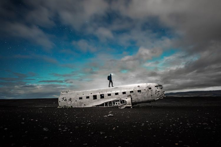 Silhouette Man Standing On Abandoned Airplane At Beach Against Cloudy Sky At Night