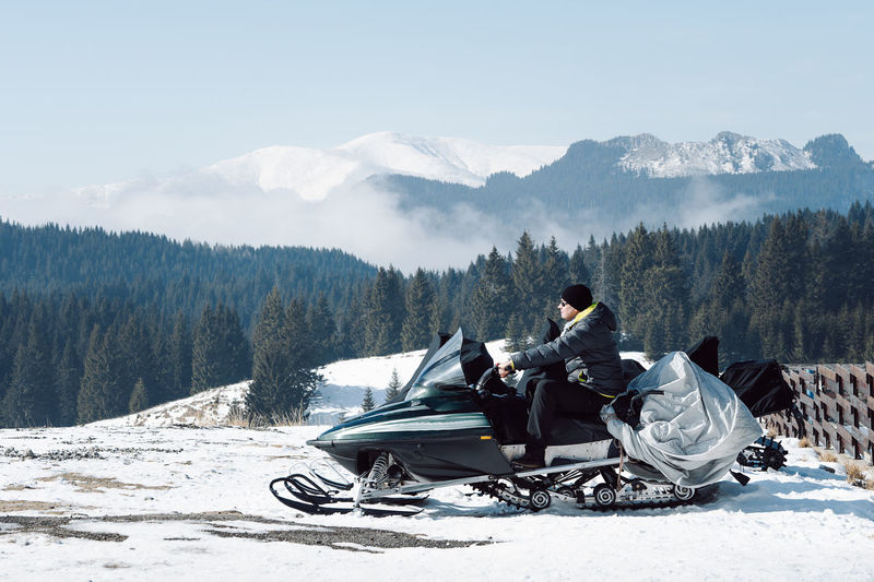 Man sitting on snowmobile in front of snowcapped mountains against sky