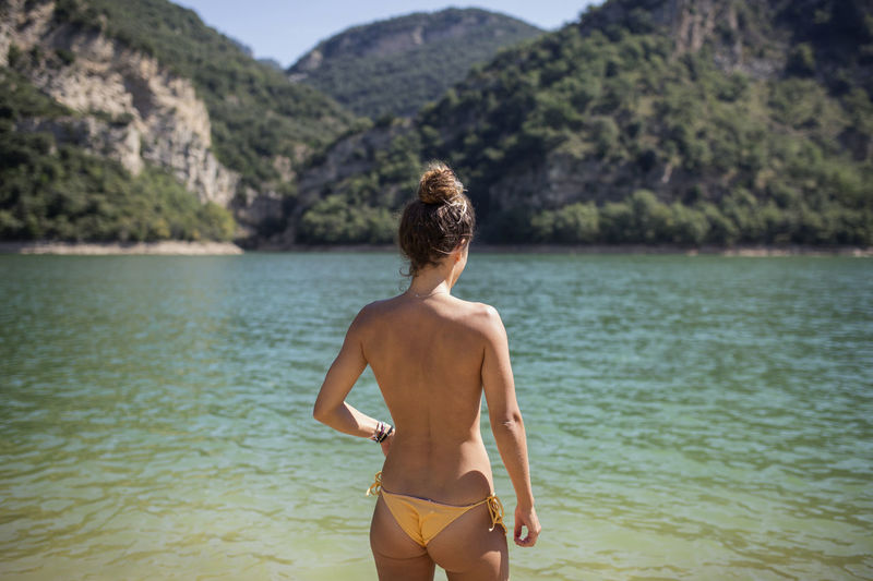 Rear view of shirtless woman looking at lake