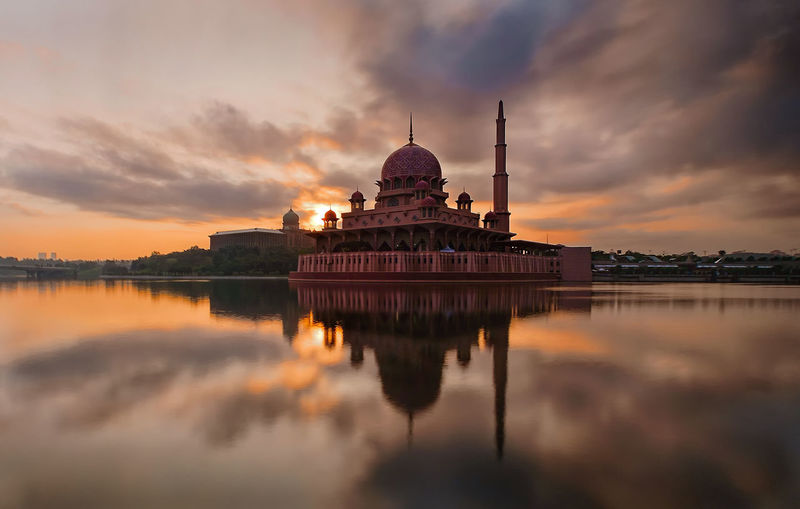 Reflection of putra mosque on calm lake against sky during sunset
