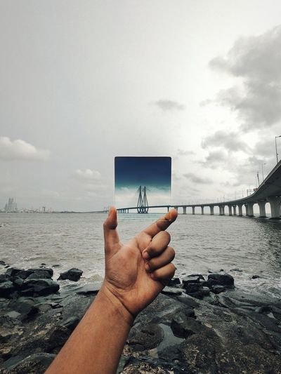 Midsection of person holding sea against sky