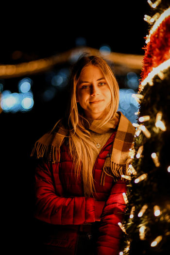 Portrait of smiling young woman standing by illuminated christmas tree at night