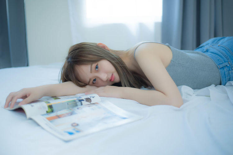 Portrait of woman lying on bed at home