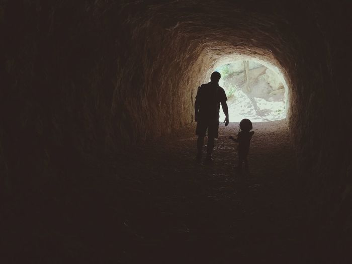 Silhouette Father With Daughter Standing In Cave
