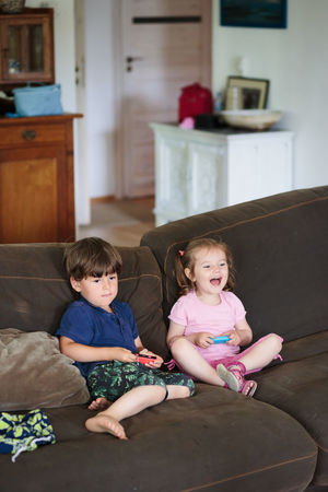 Toddlers boy and girl playing video game sitting on sofa at home Brother Children Family Fun Home Playing Games Relaxing Siblings Sister Boy Child Childhood Cute Game Girl Home Interior Indoors  Joy Lifestyles Playing Real People Sibling Sitting Toddler  Video