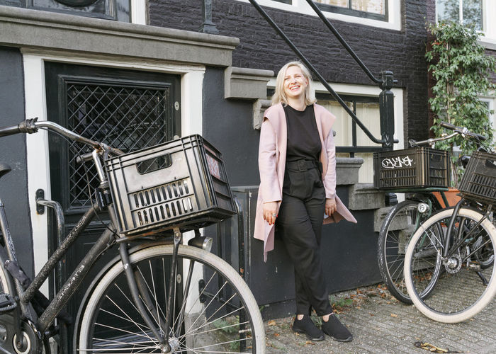 Portrait of happy woman standing on bicycle