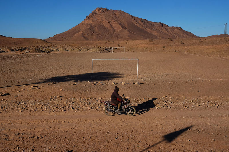 Person with umbrella on desert against sky
