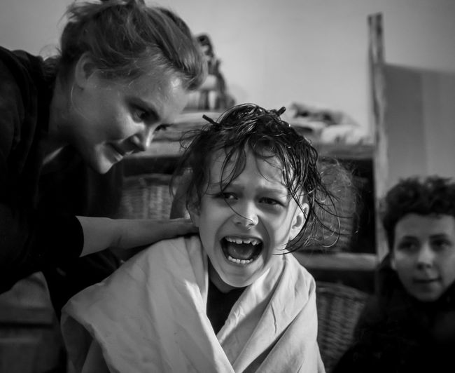 Portrait of mother cutting kid's hair