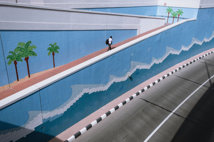 A man is walking along street wall designs in Dubai, U.A.E. Architecture Architecture_collection Blue Wave Dubai Architectural Feature Architecture Architecturelovers Art Blue Design Outdoors Pattern Street Street Art Street Photo Street Photographer Street Photography Streetart Streetphotography