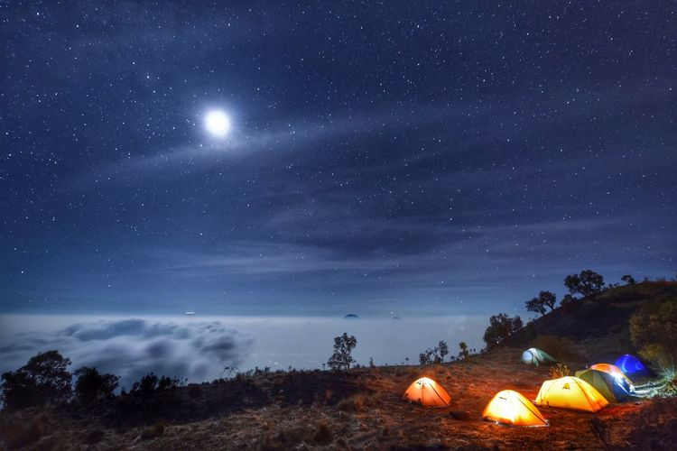 Illuminated Tents On Mountains Against Star Field At Night