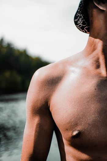 Midsection of shirtless man standing in water against sky
