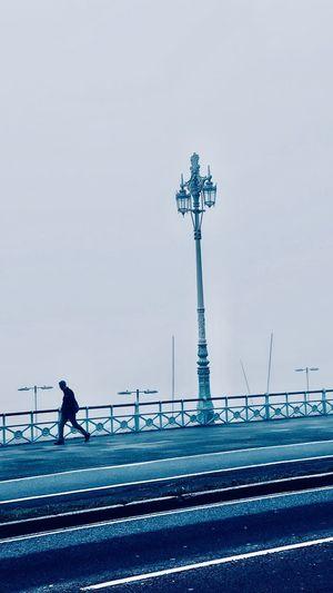 Man walking on road against sky in city