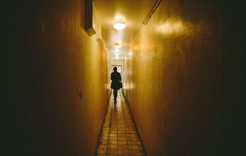 Man standing on illuminated corridor