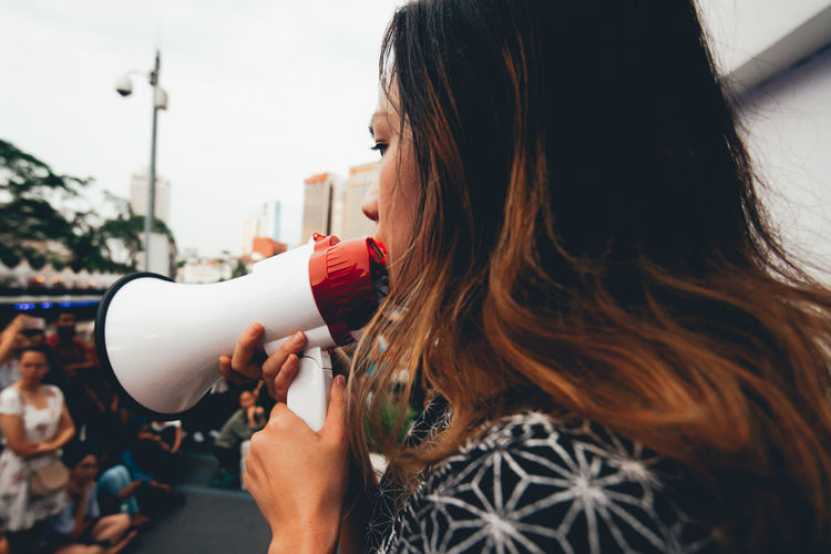 Side view of woman talking on megaphone on city street