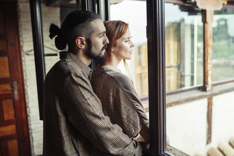Young couple standing by window in winter