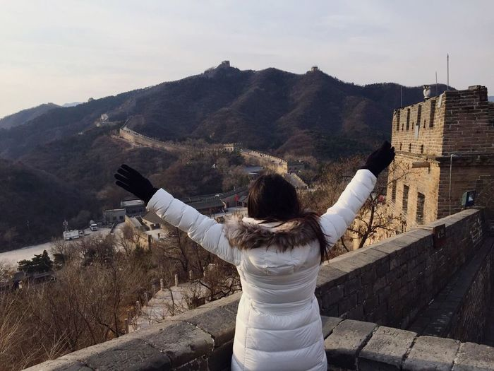 Rear view of woman with arms outstretched standing against great wall of china
