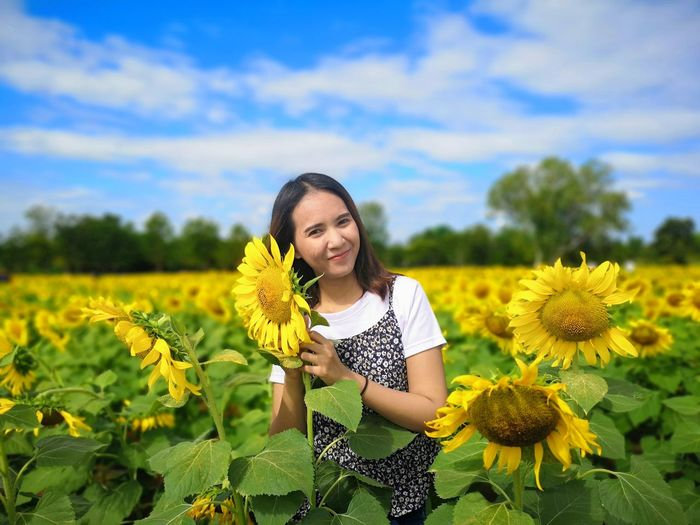 Portrait of a smiling young woman in sunflower field