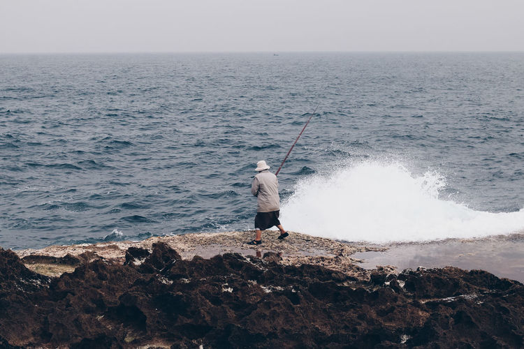 Full length of man fishing in sea against sky