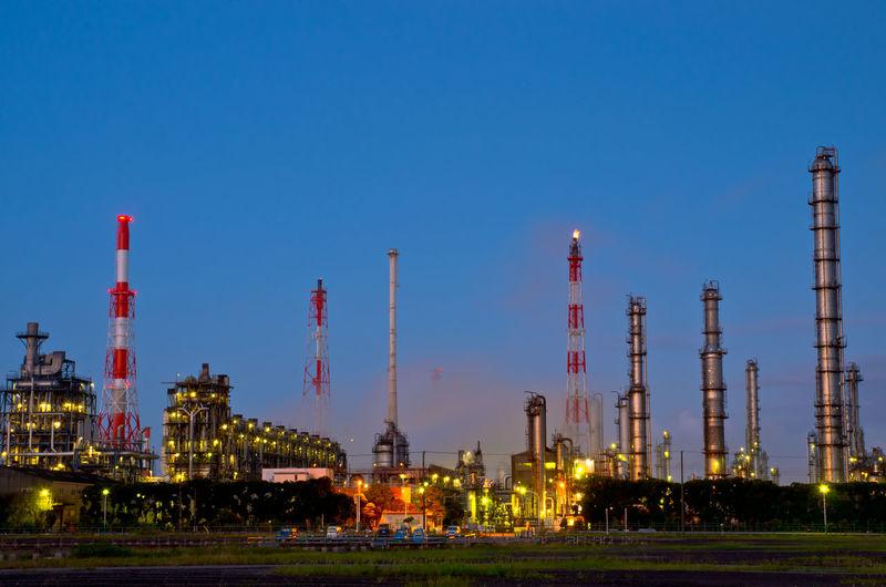 Illuminated factory against blue sky