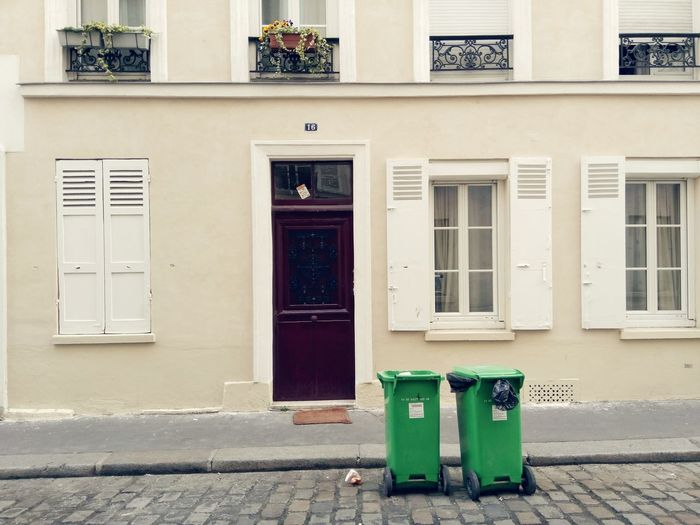 Garbage cans against building