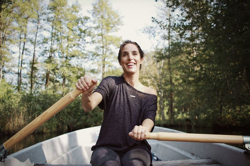 Mid Adult Woman Rowing Boat On River In Forest